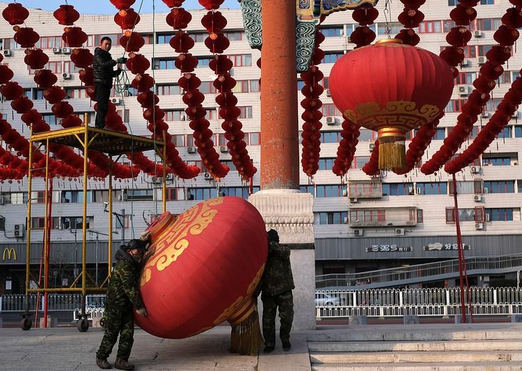 Рабочие демонтируют украшения на ярмарке к предстоящему Лунному новому году после новостей об её отмене, Пекин.