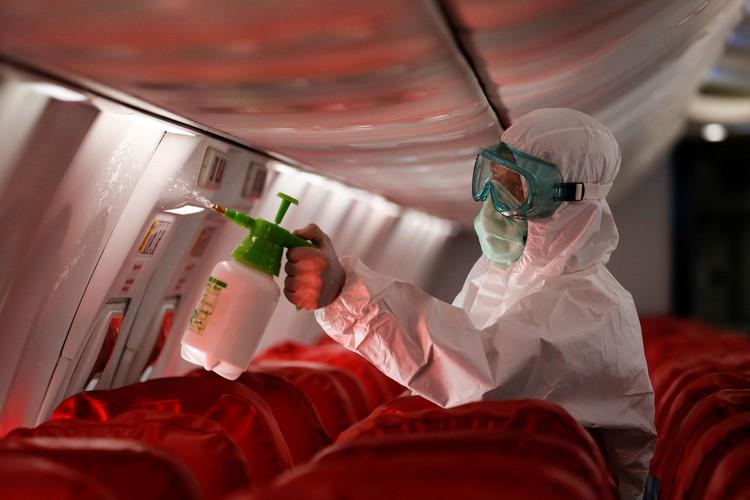 Сотрудники службы аэропорта проводят дезинфекцию салона в аэропорту Джакарты.