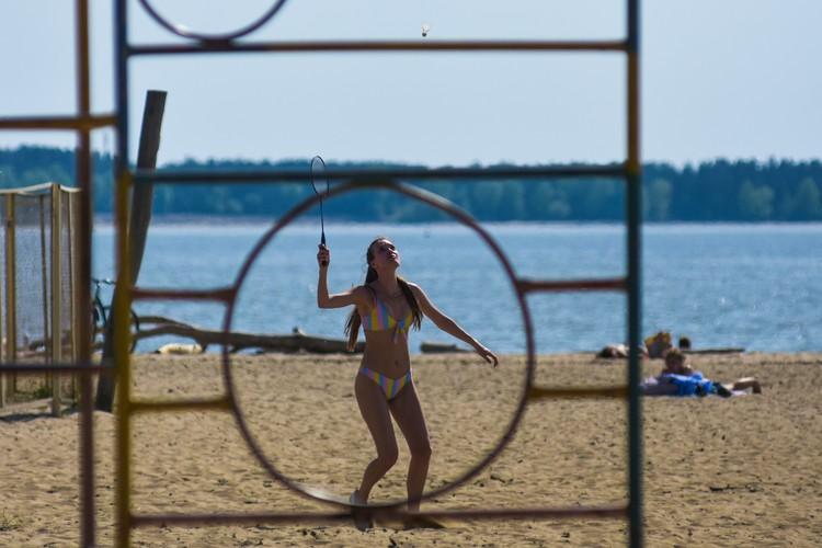 Несмотря на жару, молодые люди играют на раскаленном песке в бадминтон.