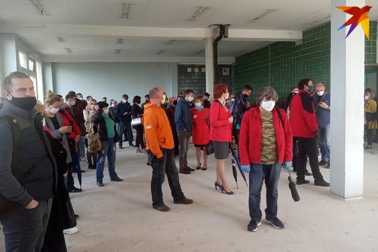 Люди собирались в просторном помещении с бетонным полом и голыми стенами.