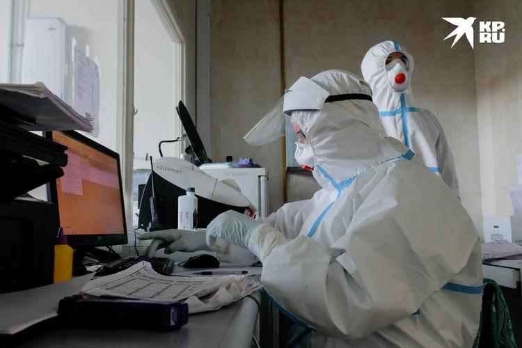 Работать за компьютером медики могут и в защитных костюмах