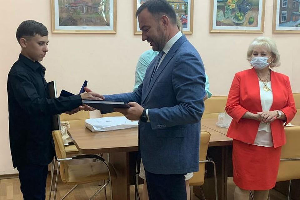 Виталий Барышников награждает Славу. Фото: пресс-служба администрации Иркутска.