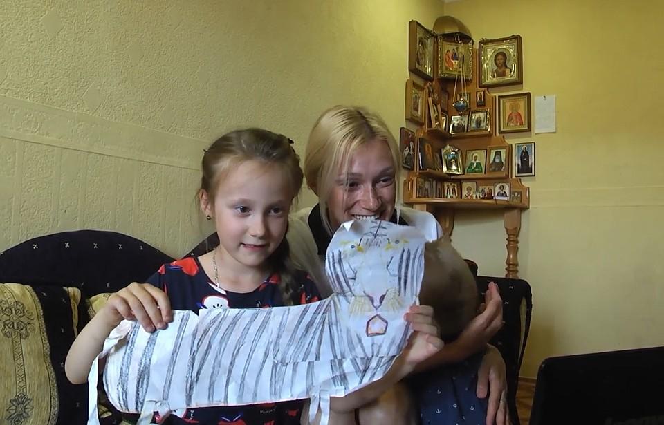Дочка показывает отцу тигра из бумаги. По всей видимости теперь у девочки тигр любимое животное
