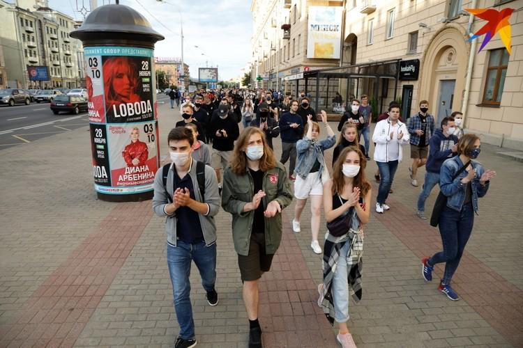 Группа людей аплодируя двигалась по проспекту Независимости им вслед сигналили проезжающие мимо автомобили.
