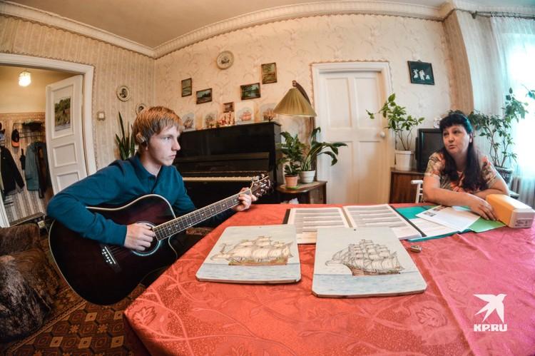 Парень профессионально играет на гитаре и фортепьяно.