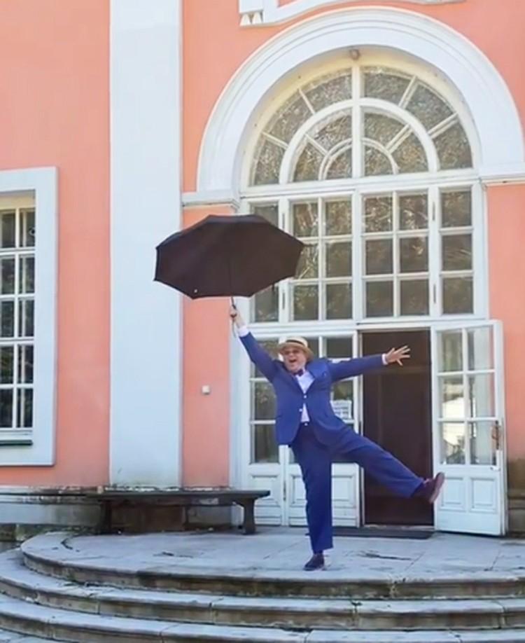 Во время фотосессии Петросян прыгал с зонтиком на ступеньках усадьбы. Фото: кадр видео.