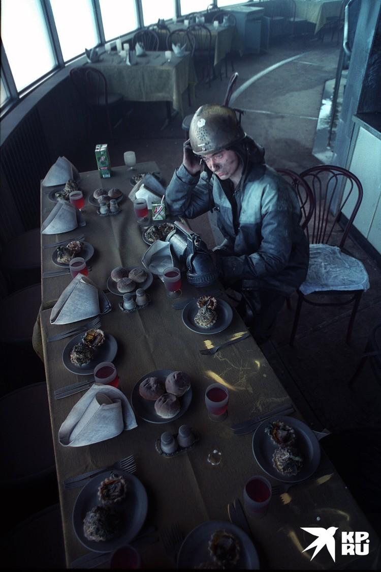 Сюрреалистическая картина в ресторане после пожара: сервированные столы покрыты пеплом и копотью, как и спасатель, который присел отдохнуть.