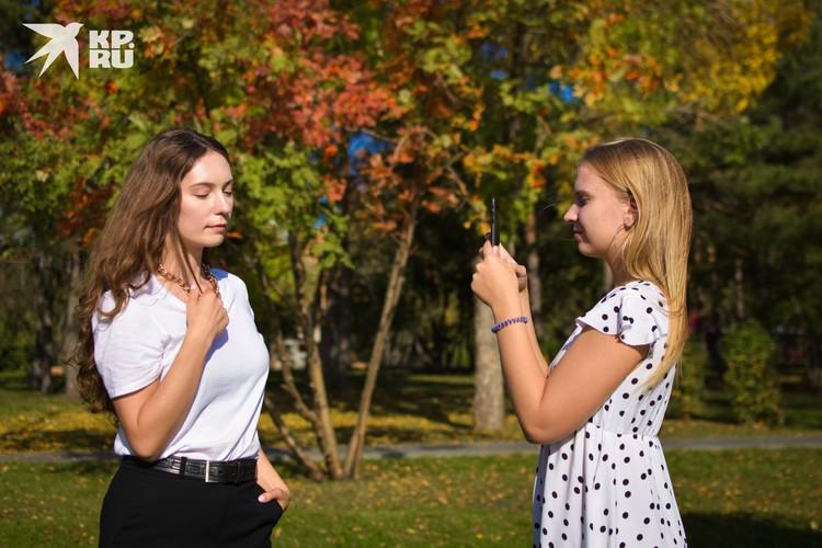 Подружки фотографируют друг друга на фоне осенних деревьев.