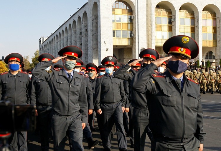 Кыргызские полицейские проходят строем по площади Ала-Тоо после того, как президент Сооронбай Жээнбеков объявил чрезвычайное положение в столице и приказал ввести туда войска