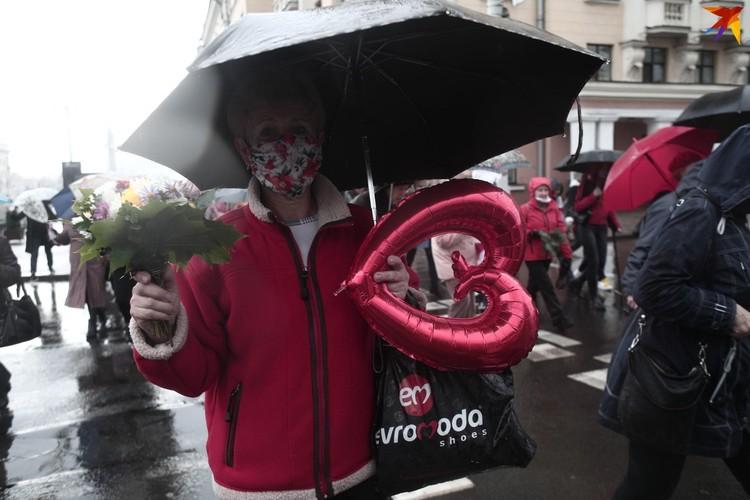 Осенний букет и шарик в виде сердечка взяла женщина на акцию матерей.