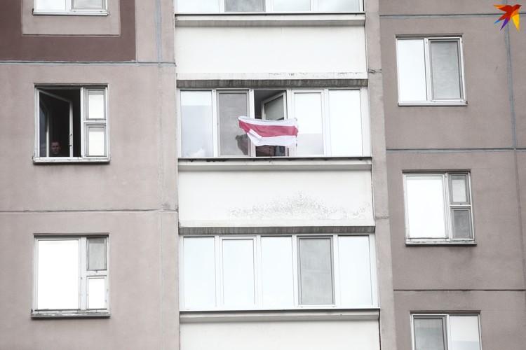 На балконе люди махали бело-красно-белым флагом.