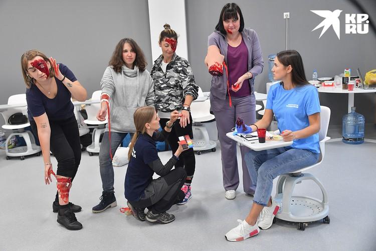 Сначала подготовка. Часть учителей внутри кабинета с помощью бинтов, макияжа, грима и клубничного варенья «наносят» друг другу травмы