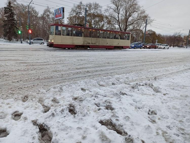 Пешеходы идут по снежной каше.