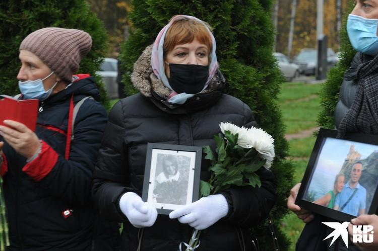 У мемориала собрались десятки человек с цветами и фотографиями погибших близких в руках.
