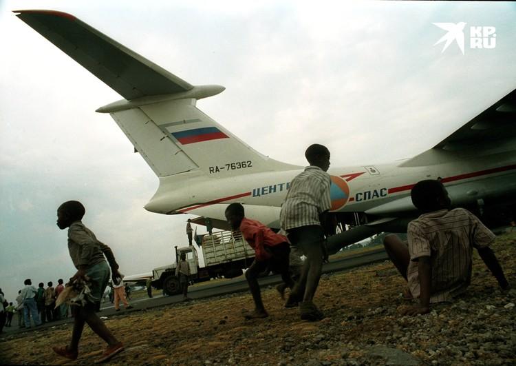Африканские дети радостно приветствуют самолет МЧС с продовольственной помощью прибывшей для народа Руанды. Июль 1995 года