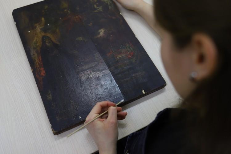 : На этой иконе нанесен защитный слой — олифа. Со временем она сильно темнеет. На фото реставратор снимает его специальным растворителем, чтобы открыть изображение автора