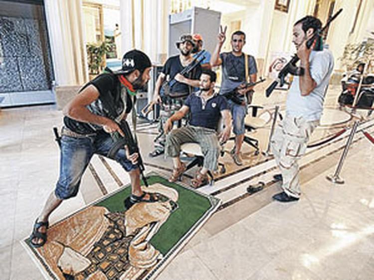 Повстанцы ворвались в резиденцию Каддафи и с удовольствием позируют на фоне лика «поверженного тирана»