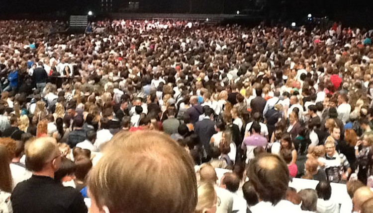Тысячи поклонников смотрят за происхдящи м на сцене