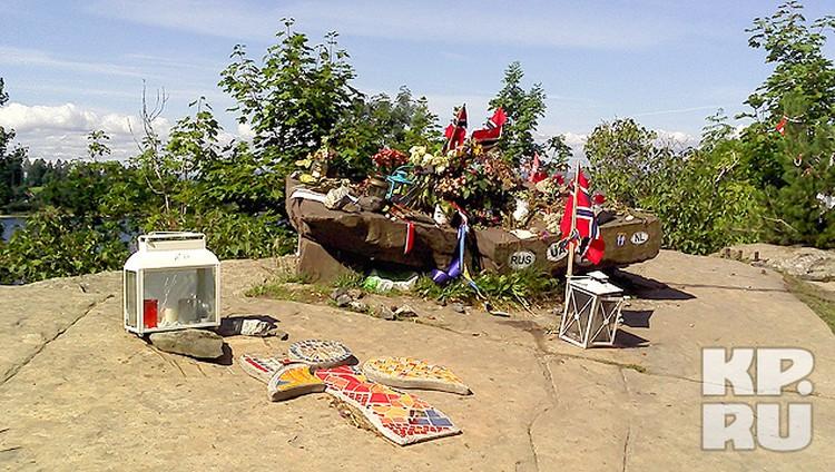 На камне, с котрого виден остров, норвежцы устроили мемориал. Так он выглядит сегодня: свечи, флаги...