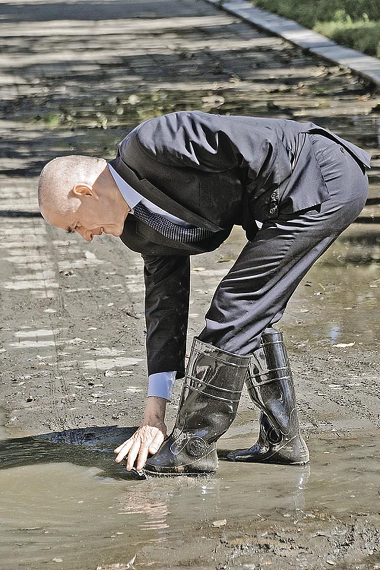Казалось, главный санитарный врач стремился проверить качество всего на свете. Даже российской грязи (на фото он в затопленном Хабаровске).